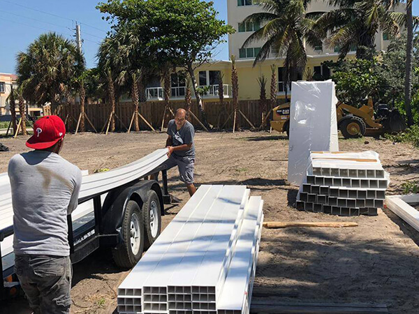 Two fence installers while starting a white fence project in Fort Lauderdale