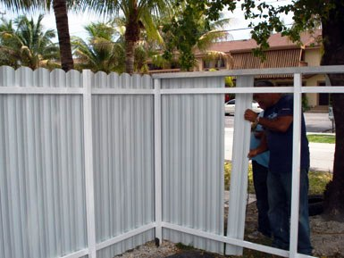 One of our staff members installing a privacy metal fence in Fort Lauderdale